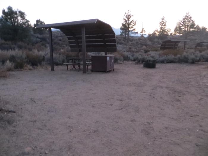 Tuff Campground site #26 featuring the shaded picnic area with camping space and fire pit by the mountain side.