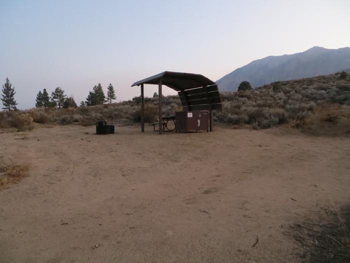 Tuff Campground site #27 featuring the shaded picnic area with camping space and fire pit by the mountain side.