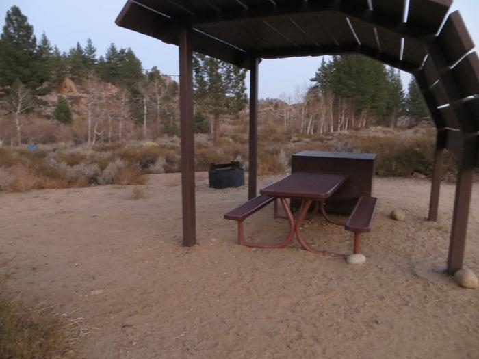 Tuff Campground site #28 featuring the shaded picnic area with camping space and fire pit by the mountain side.