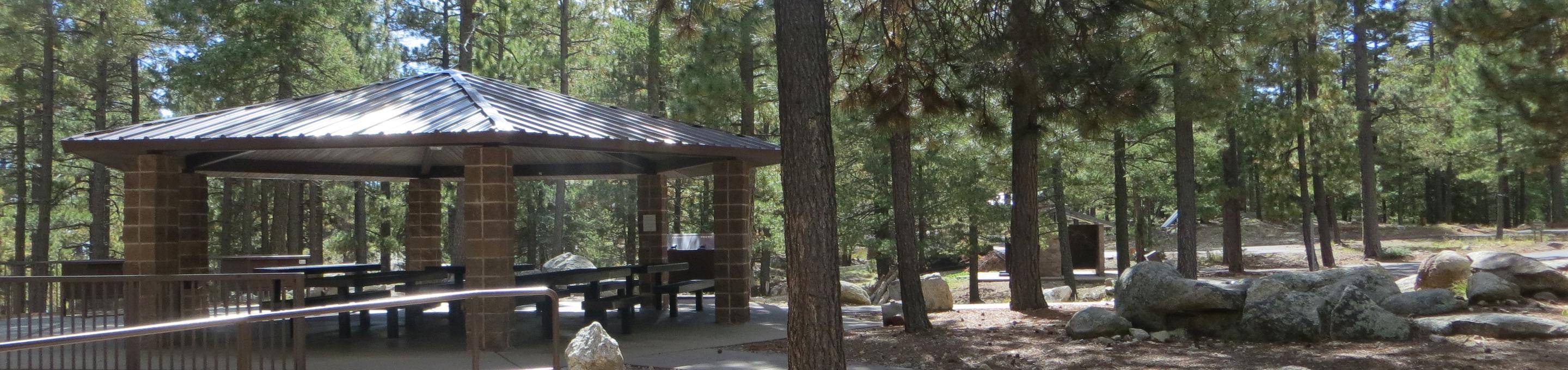 Whitetail Campground Group Site #04 featuring large ramada with multiple picnic tables, camping spaces, and food storage.