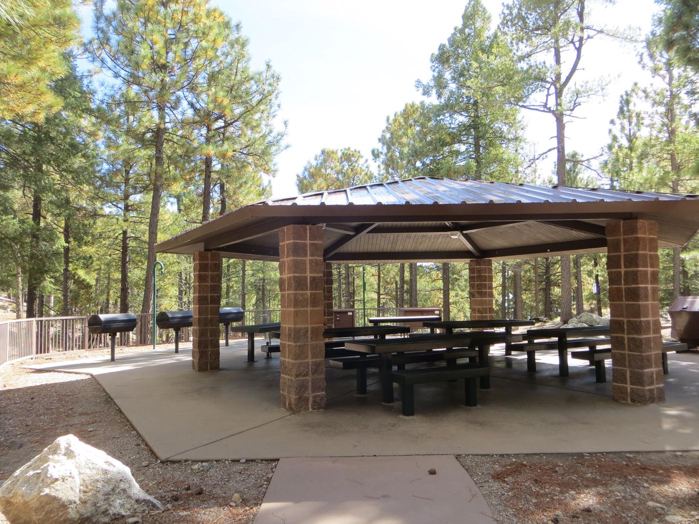 Whitetail Campground Group Site #04 featuring large ramada with multiple picnic tables and food storage.