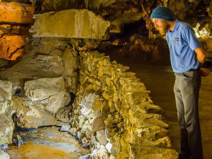 A Sequoia Parks Conservancy Naturalist gazes into the Crystal Cave stream that flows over the polished marble bedrock inside of Crystal Cave. Crystal Cave stream.