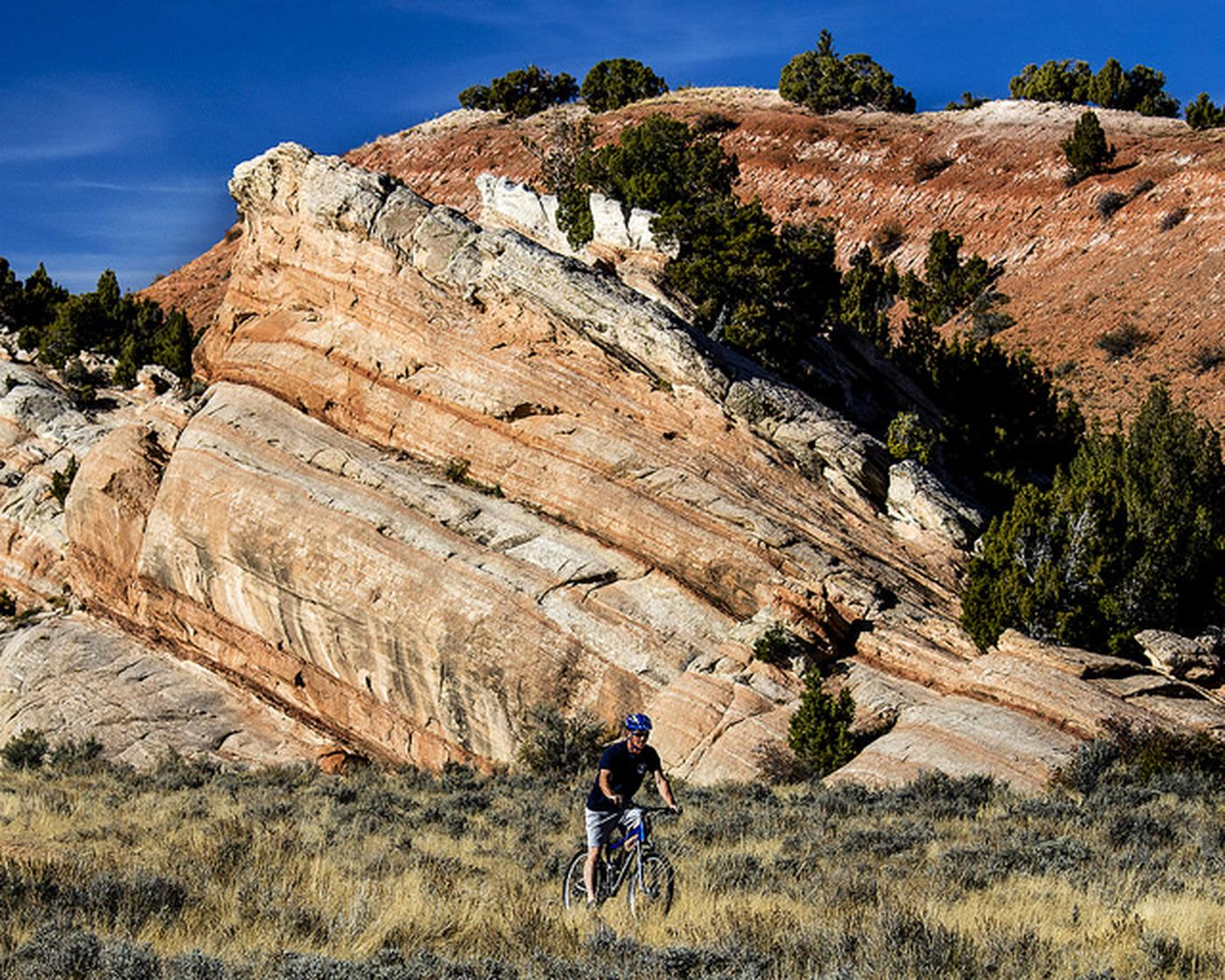 Wyoming Johnny Behind the RocksA mountain biker rides his bike in front of a red rock formation.