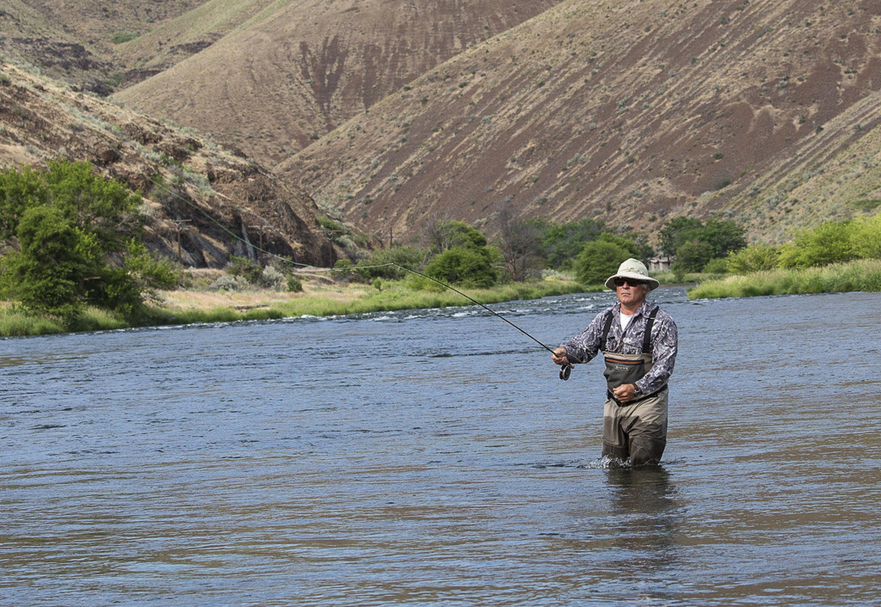 A fly fisherman tries his luck on the Deschutes river.A fly fisherman tries his luck on the Deschutes river.