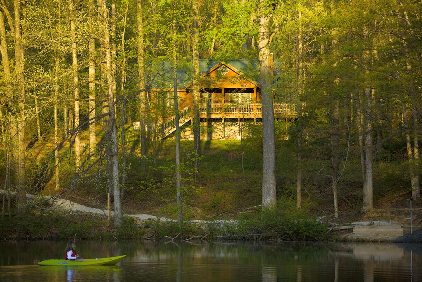 Kayaking with a view of a rental cabin at Bear Creek Lake State Park