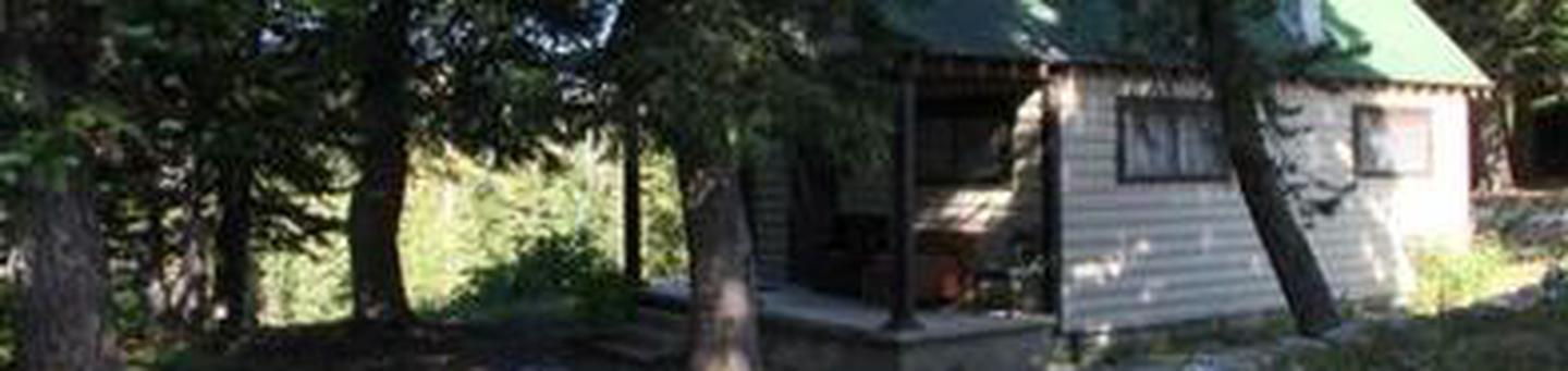 Whiite cabin with green roof located in pine treesCabin in pines