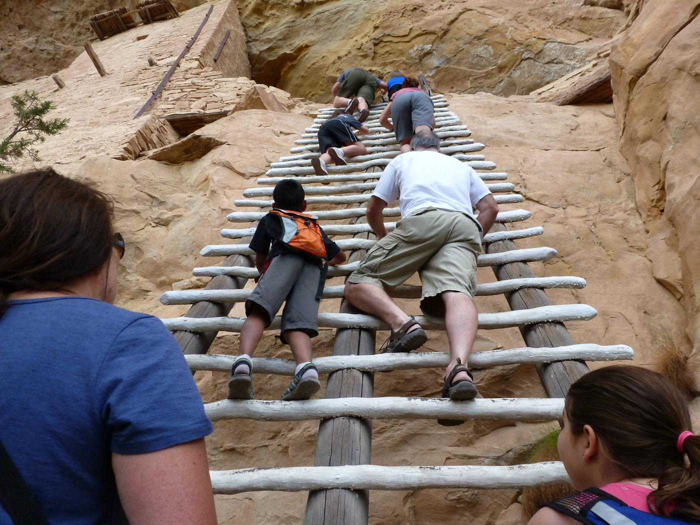 Visitors Climbing To Cliff Dwellings