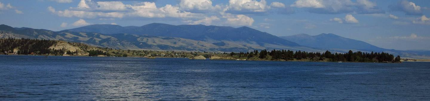 Sunny lake in forefront, mountains in the background. Canyon Ferry Reservoir