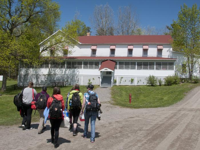 Five people are seen walking towards the painted white clapboard and red awnings of the Kettle Falls Hotel.A group approaches the historic Kettle Falls Hotel