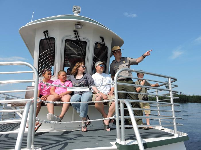A Park Ranger points a loon out to five visitors from the upper deck of the Voyageur Tour Boat
