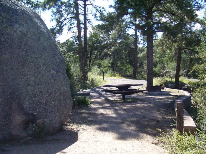 Yavapai Campground Site 1 with truck size boulder, table, fire pit on cement slab and dappled shade. Yavapai Campground Site #1