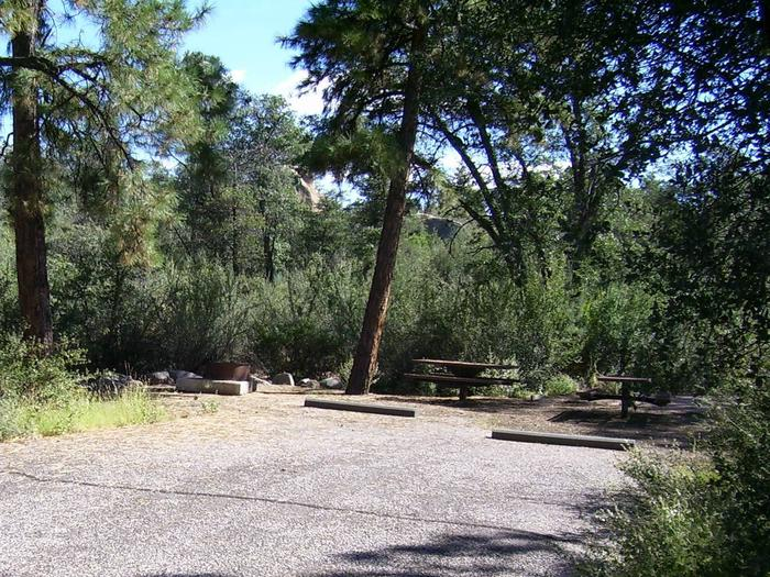 Yavapai Campground Double Site 2, with two parking spots, two tables in partial shade and a fire pit with thick vegetation in the background.  Yavapai Campground Site #2
