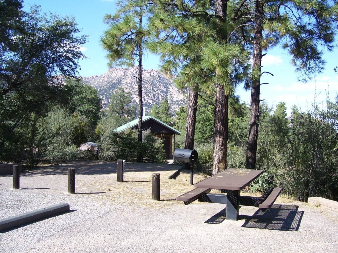 Yavapai Campground Site 6 shares parking with Site 7. Table, ballards separating parking, camping and grill area with toilet and Granite Mountain in background. Shade over tent area. Yavapai Campground Site #6