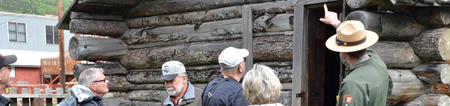 Photo of a ranger guiding a walking tour at the historic Moore CabinHistoric Moore Homestead -  Where all walking tours conclude