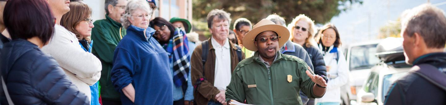 Photo of a ranger speaking to group during a Buffalo Soldier walking tourJoin us to learn about the Buffalo Soldiers who fought on two fronts: protecting the community of Skagway while facing discrimination from the same people they served.