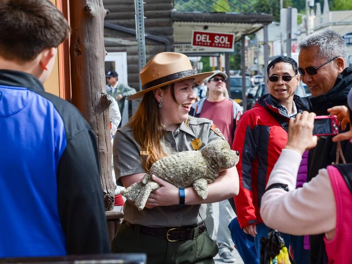 Photo of Ranger showing  a stuffed animal (seal) to a walking tourDive deeper into our history with these untold stories tours