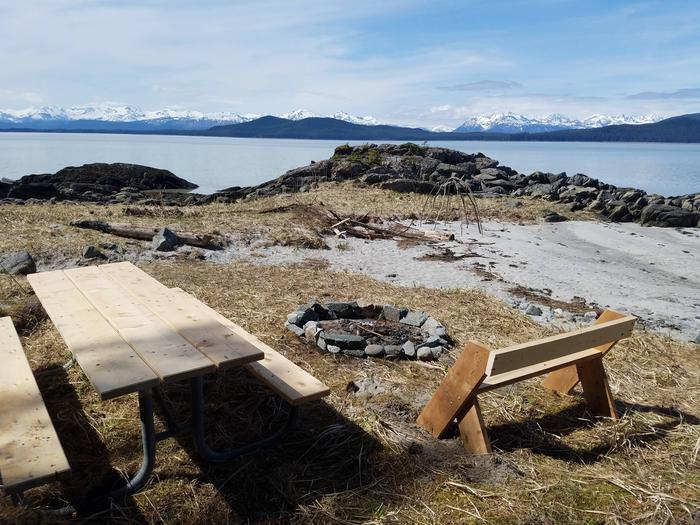 Picnic table and fire ring on sand beach