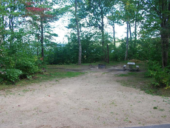 AuTrain Lake Campground site #15 full site view with table, fire pit, and picnic table.
