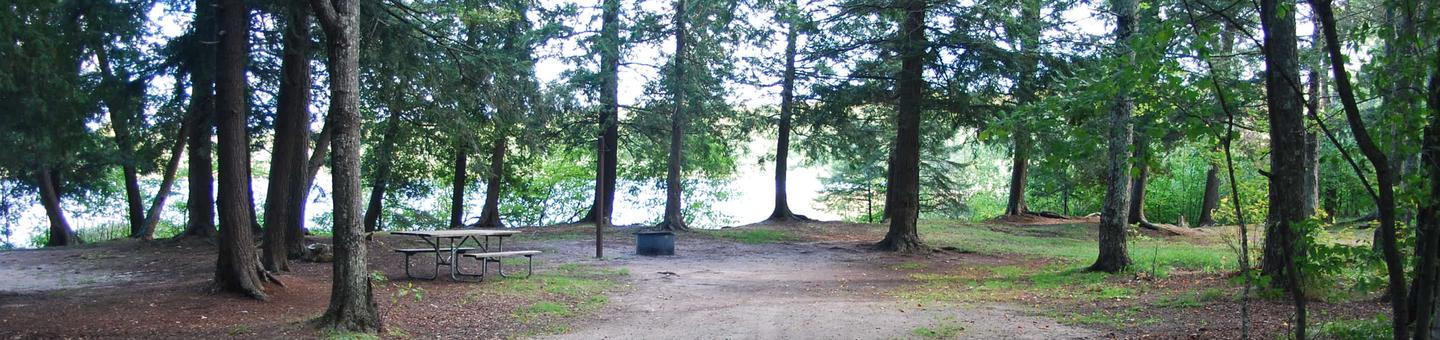 AuTrain Lake Campground site #19 full site view with table, fire pit, and picnic table.