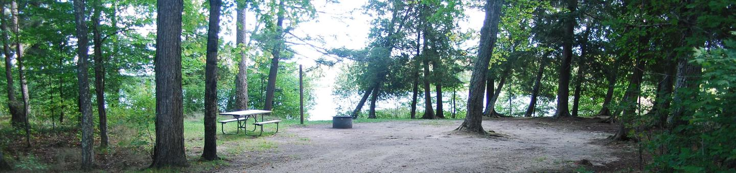 AuTrain Lake Campground site #21 full site view with fire pit and picnic table.