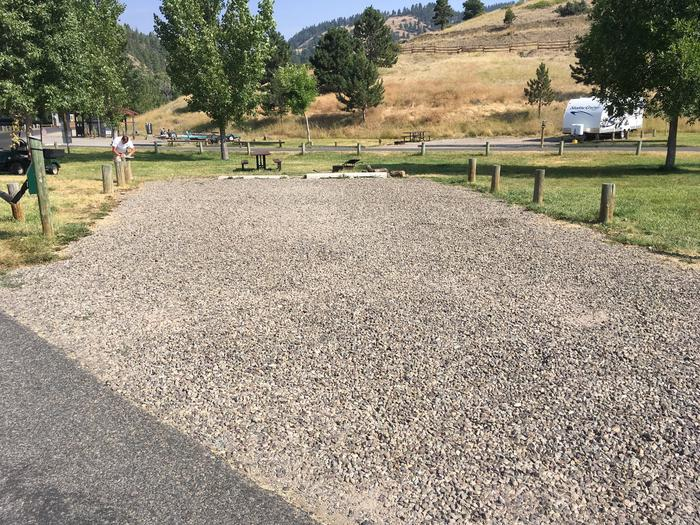Graveled surface. Grass and trees surround campsite. Easy walking distance to lake. Picnic table and firering available at site.A-1 Holter Lake Campsite