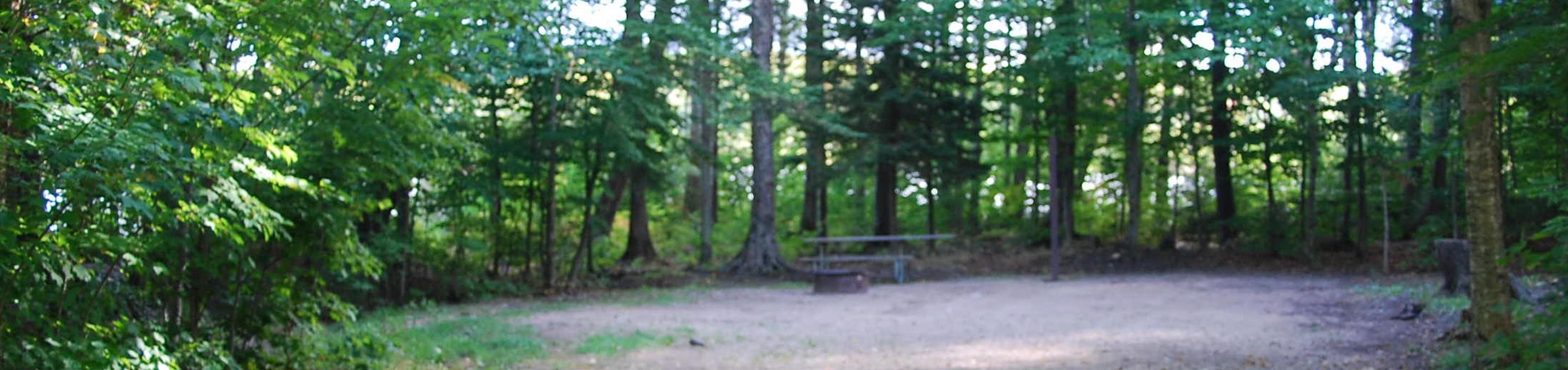 AuTrain Lake Campground site #26 full site view with fire pit and picnic table.