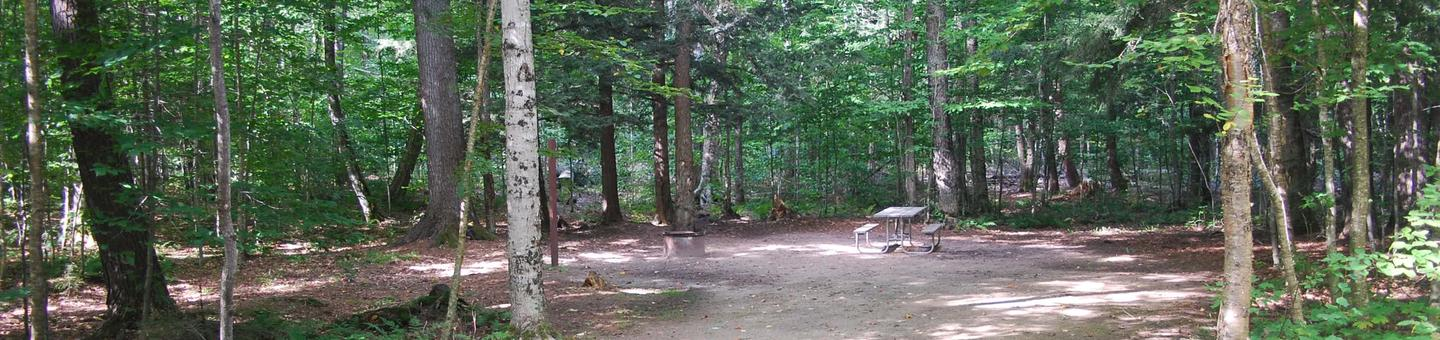 AuTrain Lake Campground site #33 full site view with fire pit and picnic table.
