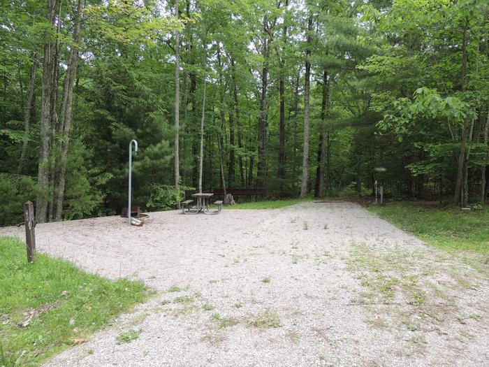 Rocky parking and tent pads with picnic table and lantern hook nearby surrounded by green treesSite 3
