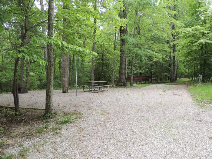 Rocky parking and tent pads with picnic table and lantern hook nearby surrounded by green treesSite 2