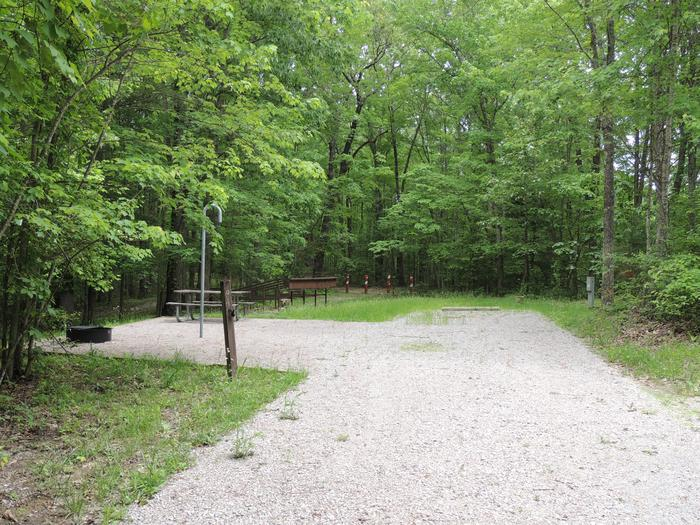 Rocky parking and tent pads with picnic table and lantern hook nearby surrounded by green treesSite 1
