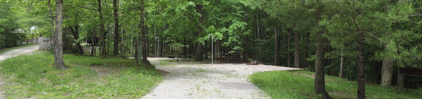 Rocky parking and tent pads with picnic table and lantern hook nearby surrounded by green treesSite 4