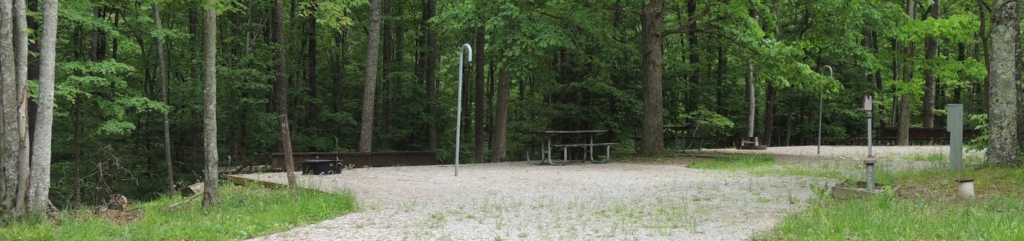 Gravel parking spot next to tent pad with picnic table and lantern hook. The site is surrounded by green trees.Site 5