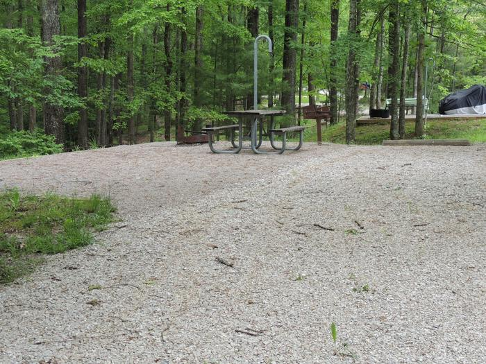 Gravel parking spot next to tent pad with picnic table and lantern hook. The site is surrounded by green trees.Site 7