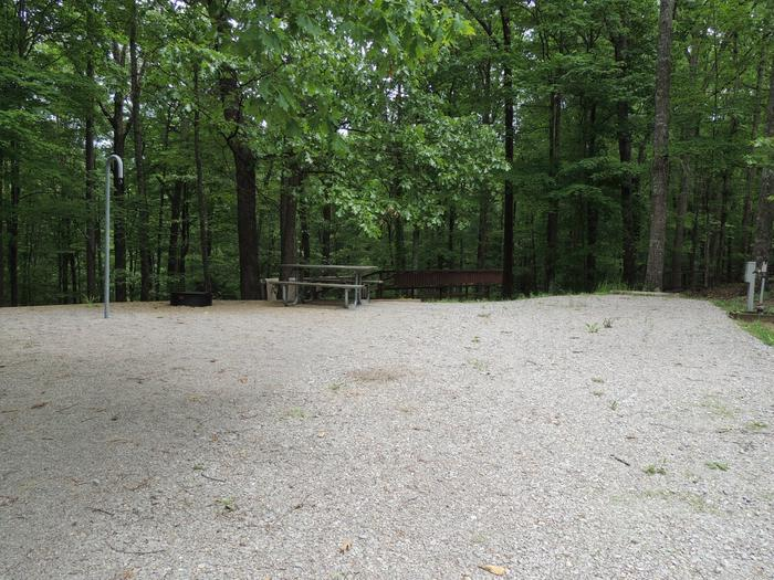Gravel parking spot next to tent pad with picnic table and lantern hook. The site is surrounded by green trees.Site 10