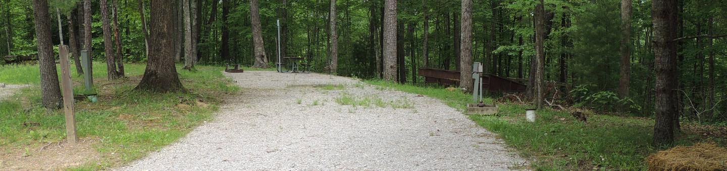 Gravel parking spot next to tent pad with picnic table and lantern hook. The site is surrounded by green trees.Site 11