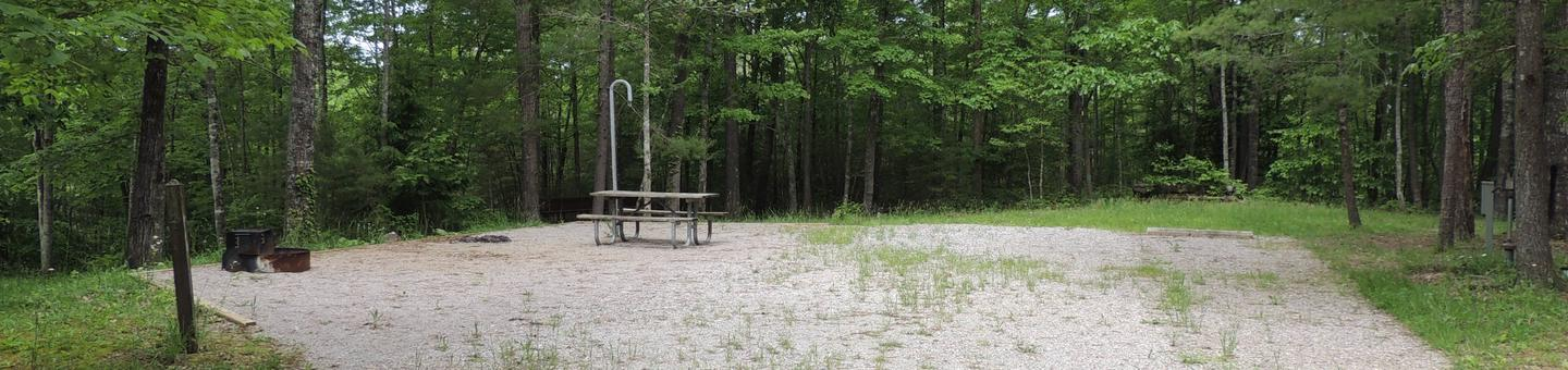 Gravel parking alongside tent pad with picnic table and lantern hook. Green trees surround the site.Site 12