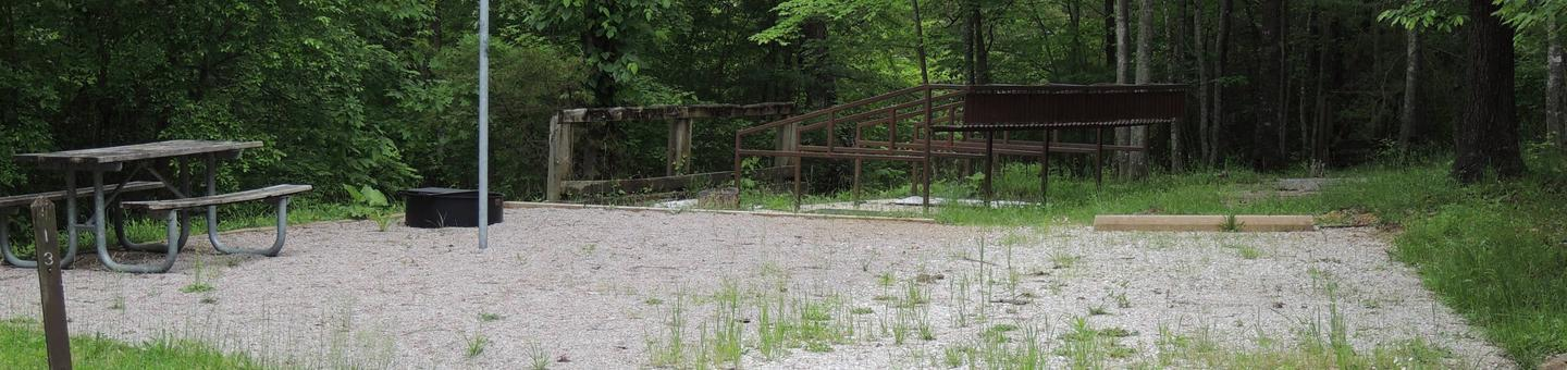 Gravel parking alongside tent pad with picnic table and lantern hook. Green trees surround the site.Site 13