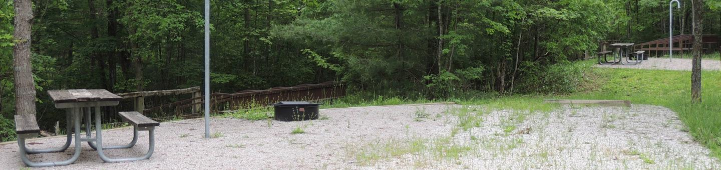 Gravel parking alongside tent pad with picnic table and lantern hook. Green trees surround the site.Site 14