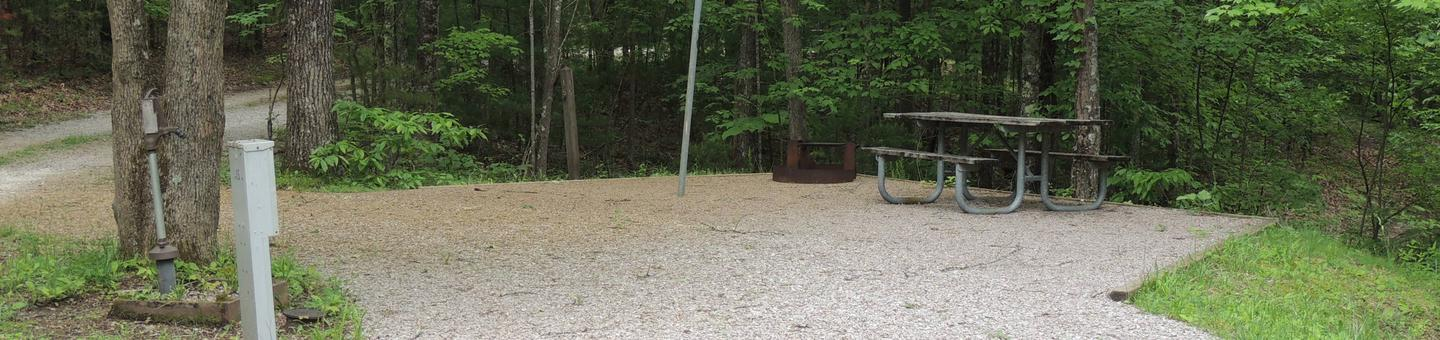 Gravel parking alongside tent pad with picnic table and lantern hook. Green trees surround the site.Site 15