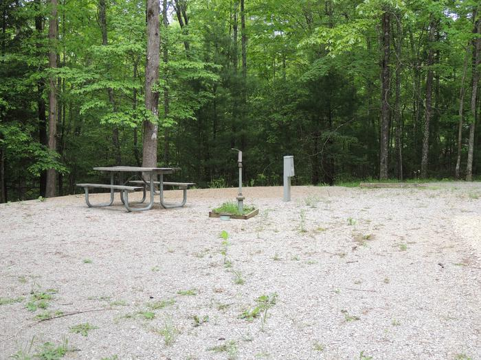 Picnic table sits next to water hydrant and electrical pedestal on gravel tent padSite 16