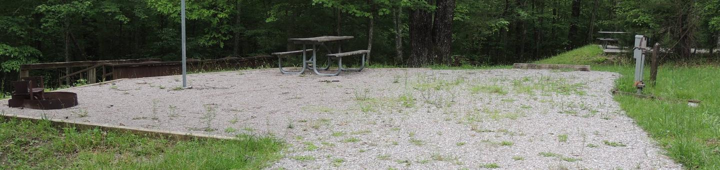 Rocky parking area next to picnic table and lantern post. Sites is surrounded by green trees.Site 18