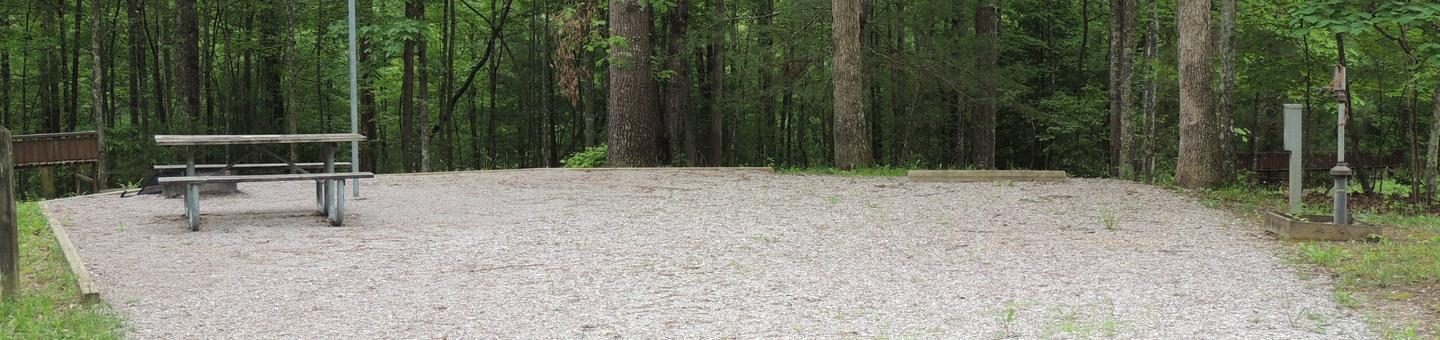 Picnic table sits on gravel tent pad surrounded by green trees.Site 21