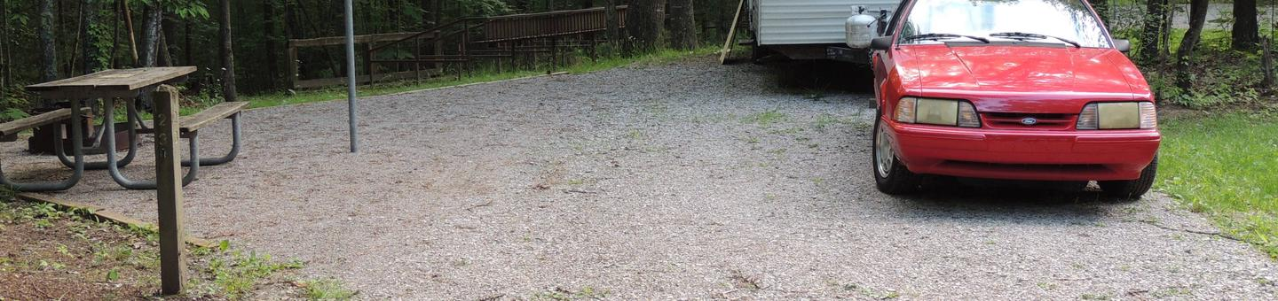 Picnic table sits on gravel tent pad surrounded by green trees.Site 23