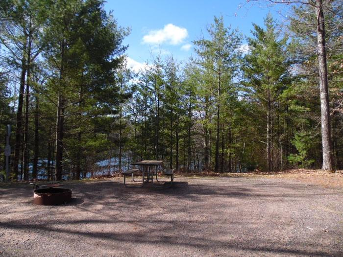 Two Lakes Campground site #65 with picnic table and fire pit view among the trees.