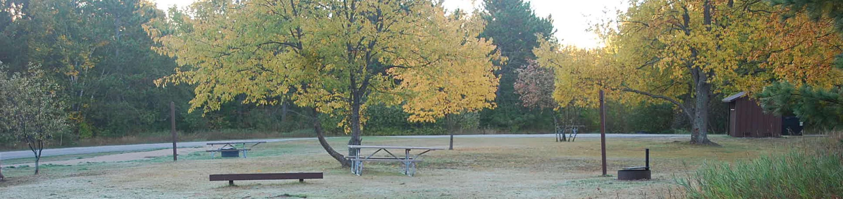 Bay Furnace Campground site #29; heavily treed site with picnic table and fire pit.