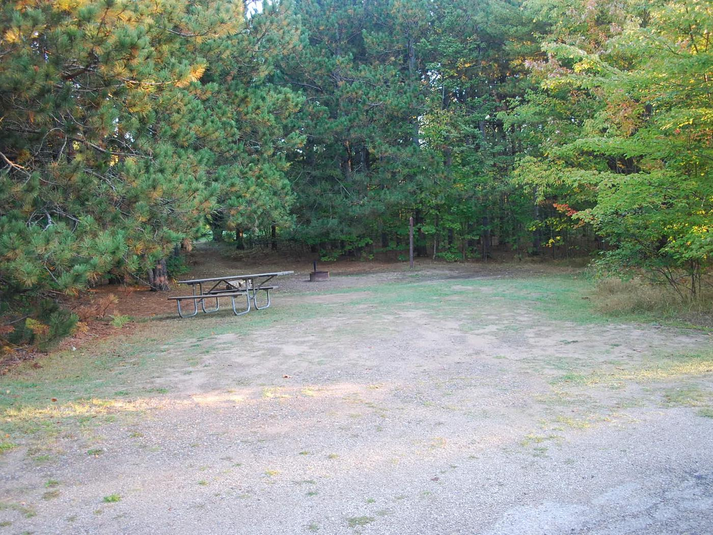 Bay Furnace Campground site #34; heavily treed site with picnic table and fire pit.