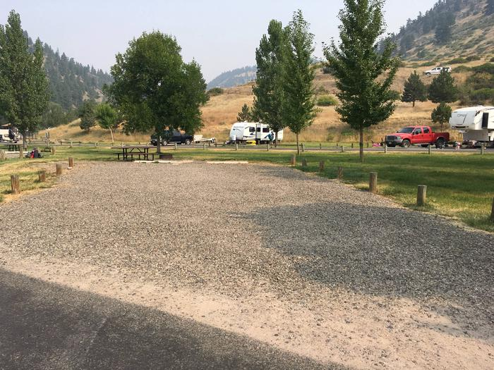 View of site 2. Graveled campsite with wooden posts bordering the edge of the graveled site. Picnic table and fire pit are available.Site 2 Campsite at Holter Lake Campground.