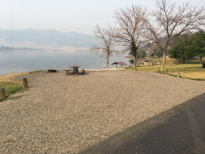 Site 3 at Holter Lake Campground. Graveled campsite with view of lake. Picnic table and fire pit on the back side of the campsite in the graveled pad. Near beach/swim area.Site 3 at BLM Holter Lake Campground.