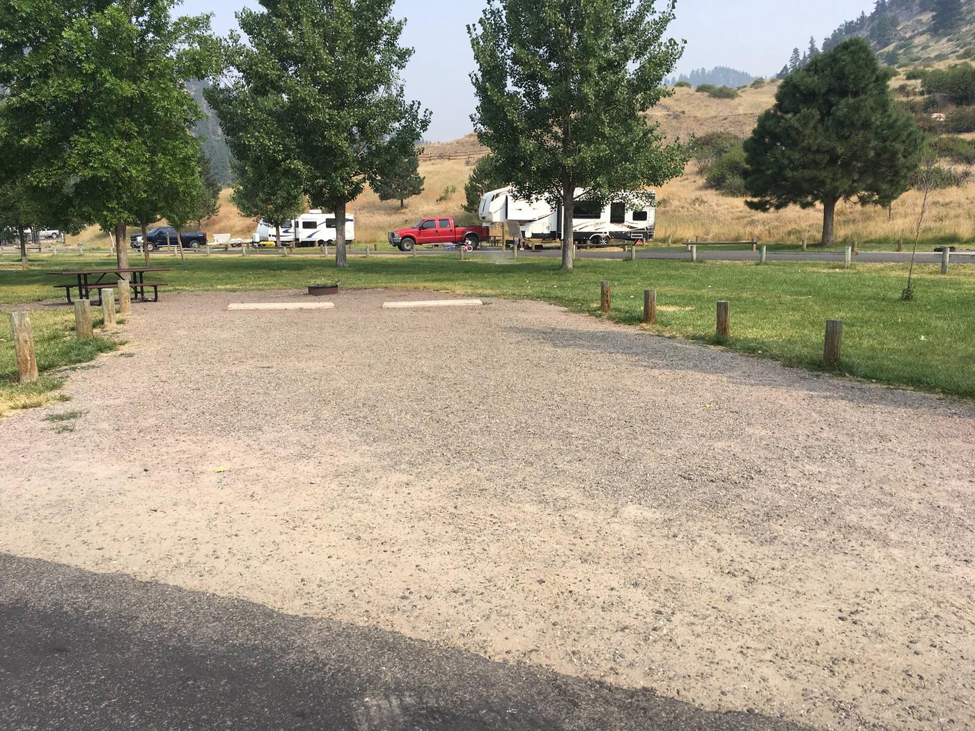 Site 4 at Holter Lake Campground. Graveled campsite with picnic table and fire pit in the background. Graveled site surrounded by wooden posts to keep parking limited to the graveled and paved surfaces. 3 large trees in the background.Site 4 BLM Holter Lake Campground.