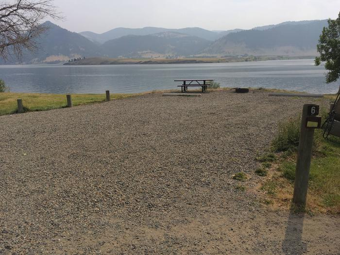 Site 6 Holter Lake Campground. View of Holter Lake. Graveled campsite with paved access. Picnic table, fire pit, and tree in the in the background. Surrounded by wooden posts.Site 6 BLM Holter Lake Campground.